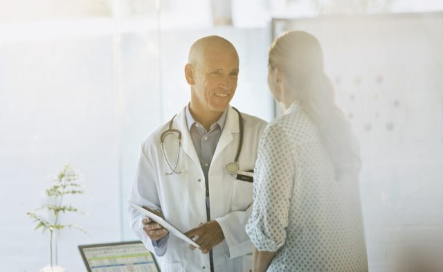 Smiling male doctor and female patient