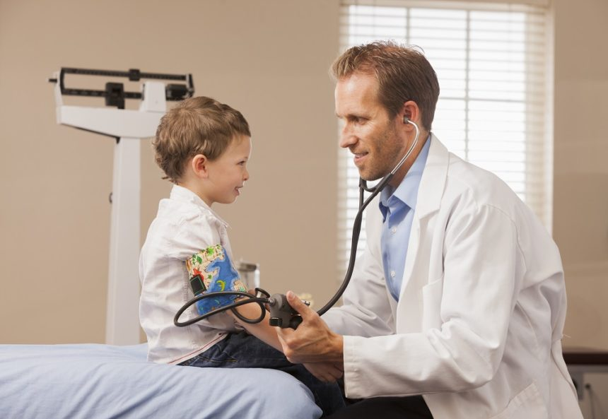 Doctor measuring blood pressure in pediatric patient