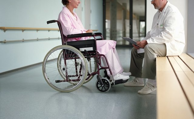 woman in a wheelchair talking to older male doctor