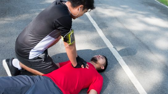 man administering CPR to another man