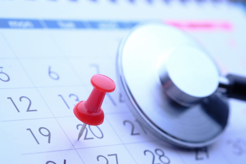 Pin and stethoscope on calendar, doctors appointment