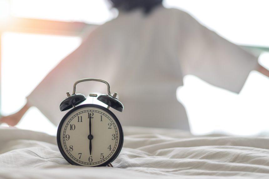 woman waking up from sleep, alarm clock