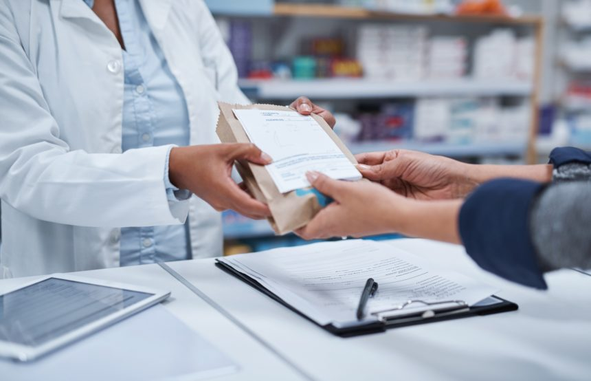 pharmacist giving prescription medicine to customer