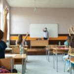 Children raise their hands while wearing masks in classroom.